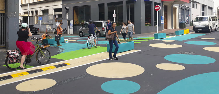 People walking across a street with giant blue and yellow circles painted on the road.