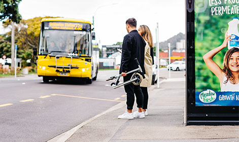 A yellow bus is pulling into the bus stop where two passengers are waiting